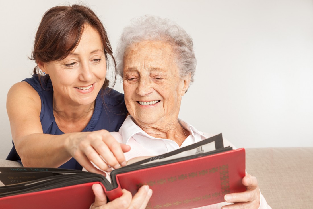 A senior and her caregiver are looking at a photo album with pleasure