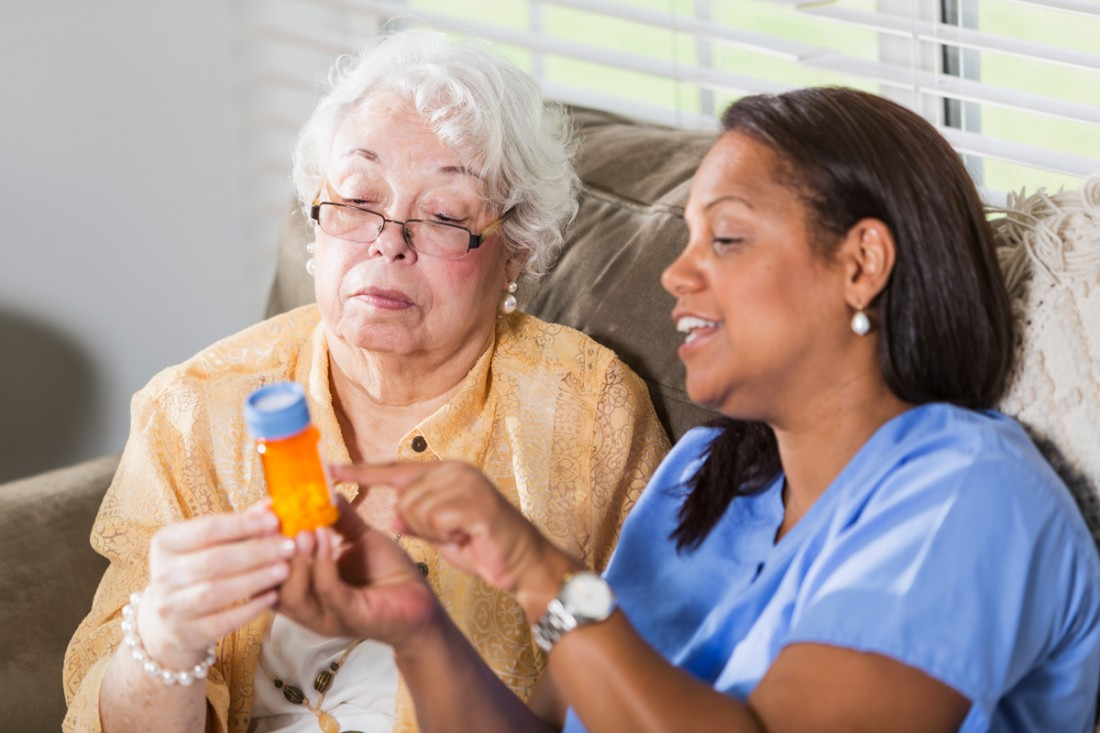 A smiling female caregiver helps a senior woman to understand her medication