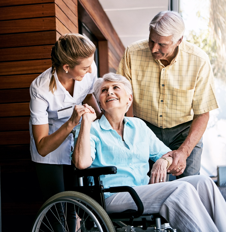 A respite care worker and a senior male hold the hands of a smiling senior woman in a wheelchair