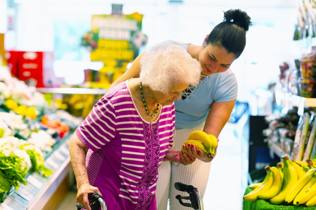 A smiling female caregiver supports a senior woman with a walker to select bananas while grocery shopping