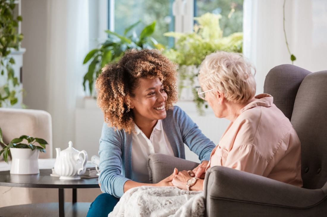 Smiling female caregiver talking with a senior in her home